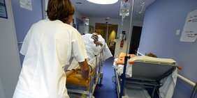 Krankenpflegerin schiebt Krankenbett mit Patienten durch einen Gang im Krankenhaus