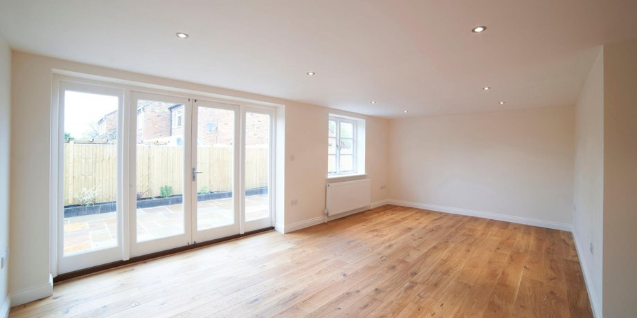 Leere Wohnung mit großen Fenstern und Parkett